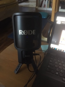 Rode NT-USB on a tripod stand next to laptop.